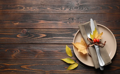 Festive table setting with autumn leaves and space for text on wooden background, flat lay. Thanksgiving Day celebration