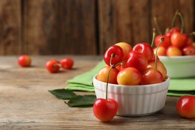 Sweet red cherries in bowl on wooden table, space for text