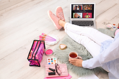 Beauty blogger with laptop and cosmetics sitting on floor, closeup
