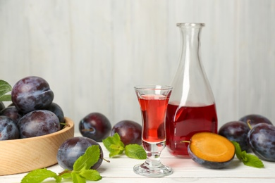 Delicious plum liquor, ripe fruits and mint on white wooden table. Homemade strong alcoholic beverage
