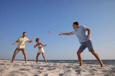 Friends playing with flying disk at beach on sunny day