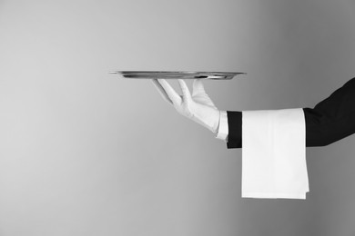 Butler with tray on light grey background, closeup. Space for text