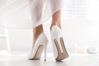 Young bride in beautiful wedding shoes walking indoors, back view