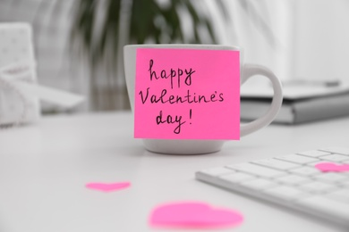 Memory sticker with phrase Happy Valentine's Day on cup at workplace