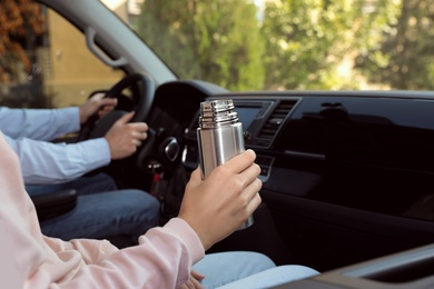 Woman with thermos on passenger seat of car, closeup