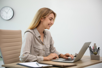 Pretty young woman working with laptop in office