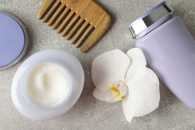 Hair care cosmetic products, orchid flower and comb on grey table, flat lay