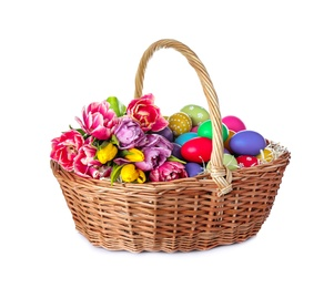 Wicker basket with bright painted Easter eggs and spring flowers on white background