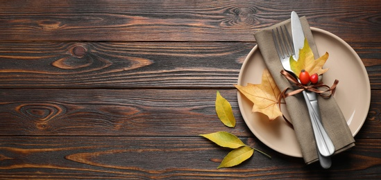 Happy Thanksgiving Day, banner design. Festive table setting with autumn leaves and space for text on wooden background, flat lay