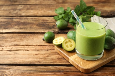 Fresh feijoa smoothie and fresh fruits on wooden table. Space for text