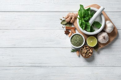 Flat lay composition with different natural spices and herbs on white wooden table, space for text