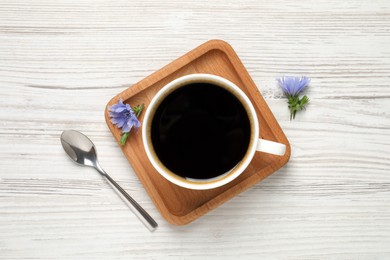 Cup of delicious chicory drink, spoon and flowers on white wooden table, flat lay