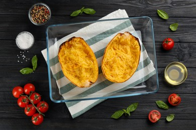 Halves of cooked spaghetti squash in baking dish and ingredients on black wooden table, flat lay