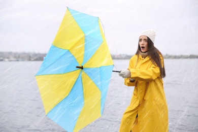 Woman in yellow raincoat with umbrella caught in gust of wind near river