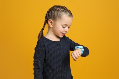 Little girl with smart watch on yellow background