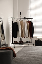Rack with stylish men's clothes indoors. Interior design
