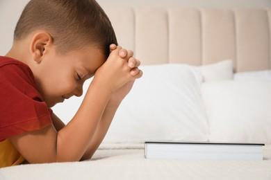 Cute little boy with hands clasped together saying bedtime prayer over Bible at home. Space for text
