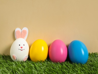 Bright eggs and white one as Easter bunny on green grass against beige background