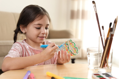 Little girl painting glass at table indoors. Creative hobby