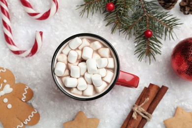 Hot drink with marshmallows, sweets and festive decor on snow, flat lay