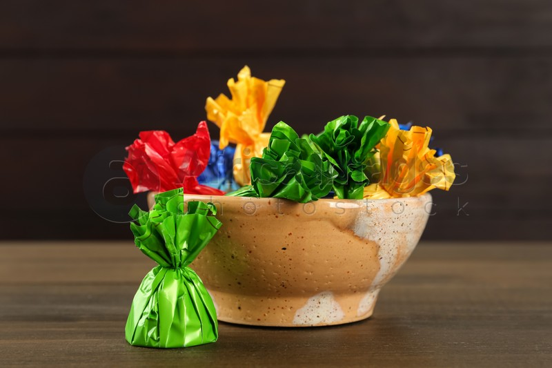 Candies in colorful wrappers on wooden table