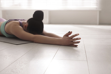 Young woman practicing relaxation pose in yoga studio