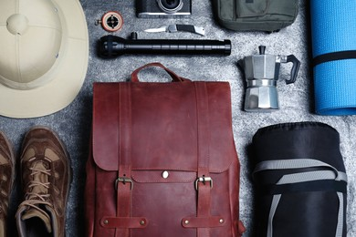 Flat lay composition with leather backpack and camping equipment for tourism on grey background