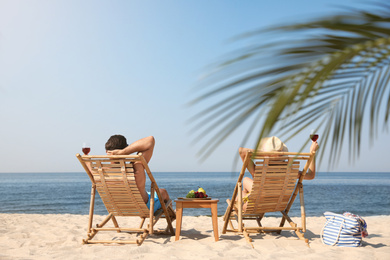 Couple with wine on sunny beach at resort