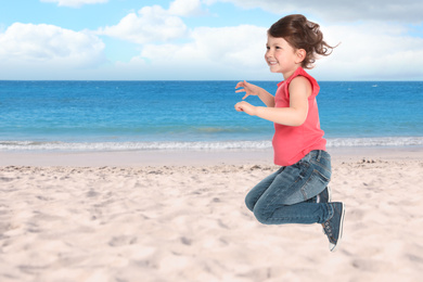 Happy school girl jumping on beach near sea, space for text. Summer holidays
