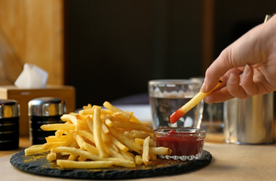 Woman dipping French fries into red sauce in cafe, closeup