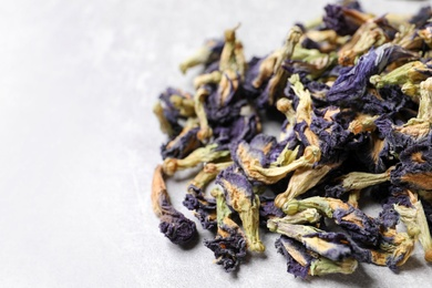 Pile of dry organic blue Anchan on light table, closeup with space for text. Herbal tea