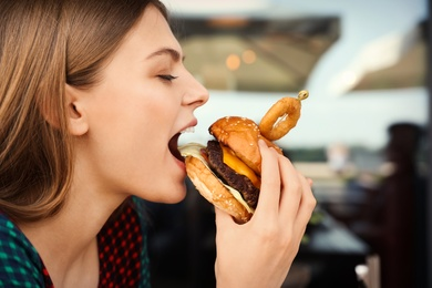 Young woman eating burger in street cafe