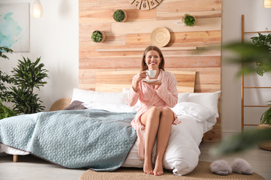 Woman drinking coffee in bedroom with green plants. Home design ideas