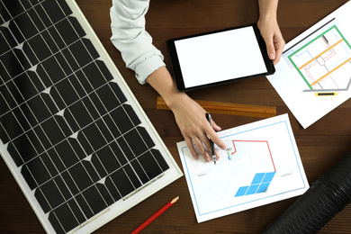 Architect working on house project with solar panels at wooden table, top view. Alternative energy source