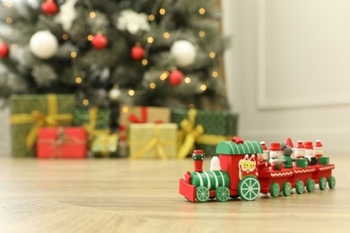 Bright toy train on floor in room with Christmas tree