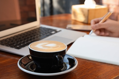 Blogger working at table in cafe, focus on cup of coffee