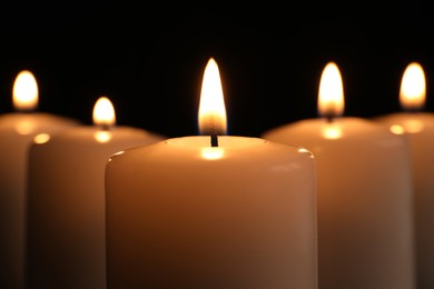 Burning candles on dark background, closeup. Memory day
