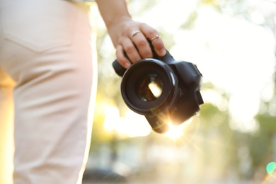 Young photographer with professional camera outdoors, closeup