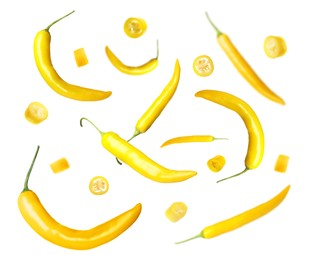 Ripe yellow chili peppers falling on white background