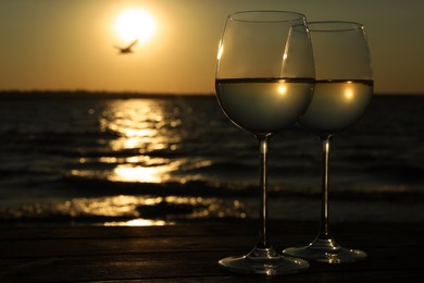 Glasses of delicious wine near sea at sunset