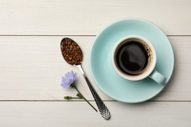 Cup of delicious chicory drink, granules and flower on white wooden table, flat lay