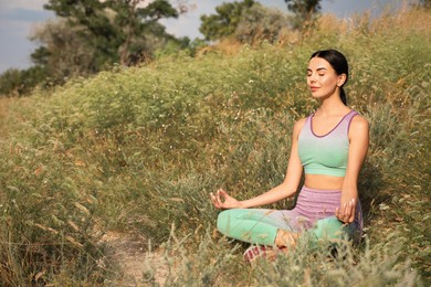 Young woman meditating on hill. Space for text
