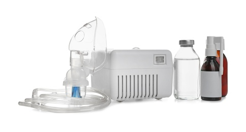 Modern nebulizer with face mask and medications on white background. Inhalation equipment