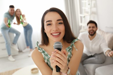 Young woman singing karaoke with friends at home
