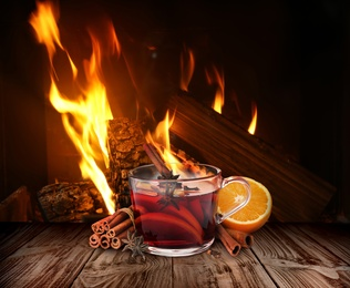 Mulled wine in glass cup on wooden table near fireplace