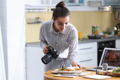Food blogger taking photo of her lunch at wooden table indoors