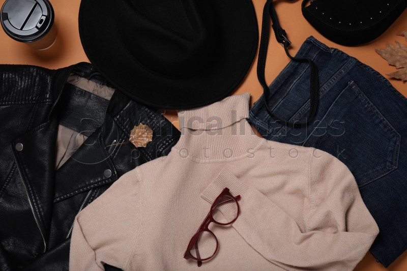 Flat lay composition with stylish hat and clothes on orange background