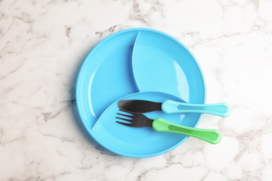 Section plate with fork and knife on white marble table, top view. Serving baby food