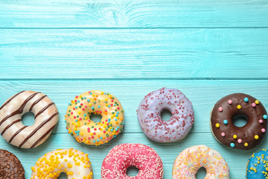 Delicious glazed donuts on blue wooden table, flat lay. Space for text