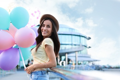 Beautiful young woman with color balloons on city street